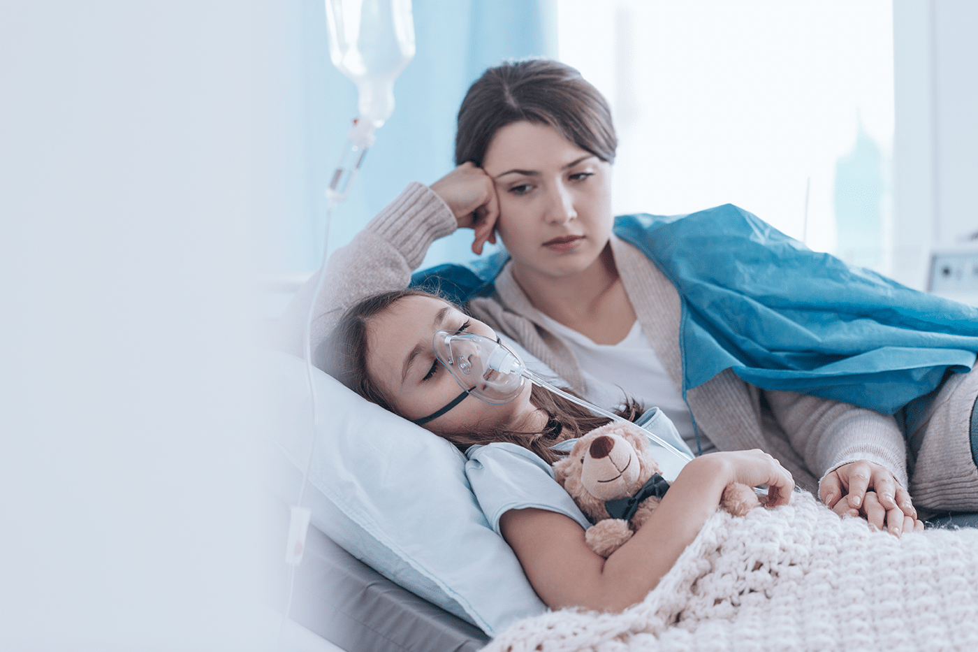 Child in hospital bed with mask on