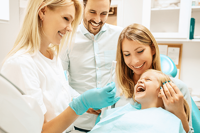 happy child with parents at dentist appointment