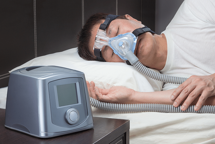Man Sleeping While Using CPAP Machine
